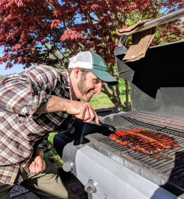 My friend's husband at the grill focusing on his seitan ribs
